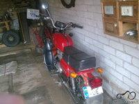 Už motociklo - nuimta nuo jo bagažinė.