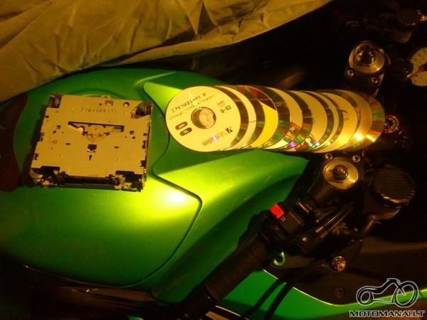 Ant motociklo padėtas išimtas CD-ROM arba DVD-ROM (optinis įrenginys, leidžiantis skaityti duomenis iš lazerinių kompaktinių diskų), ir eilute išdėlioti 16 kompaktinių diskų (be dėžučių ar įdėklų)