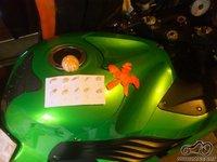 Ant motociklo 10 mandarino (arba apelsino) kauliukų, nuluptas mandarinas bei iš jo žievės padaryta (iškarpyta) žvaigždė