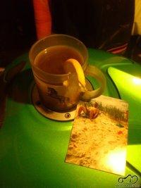 Ant motociklo stiklinis puodelis karsto vyno su citrinos grezineliu (vyno karstumas - sazines reikalas) ir nuotrauka primenanti vasara.