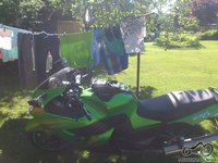 motociklas prie rubu dziovyklos lauke( stacionarios) ant virves segtukais prisegtos moto pirstines