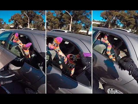 Motorcyclist squeeze the toes of a car rider with feet out the window