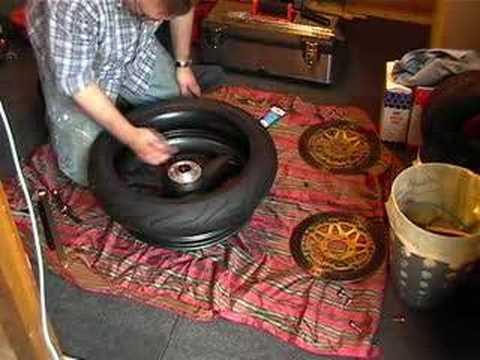 Change a motorcycle tyre by hand.